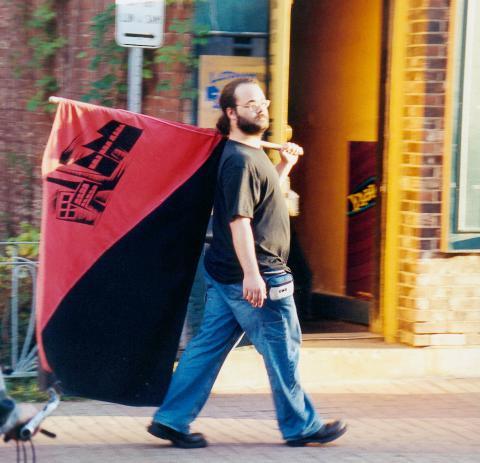 Photo : Nicolas porte un énorme drapeau rouge et noir sur lequel on disserne un dessin de domiciles. Jean, t-shirt noir, barbu, cheveux longs, lunettes.